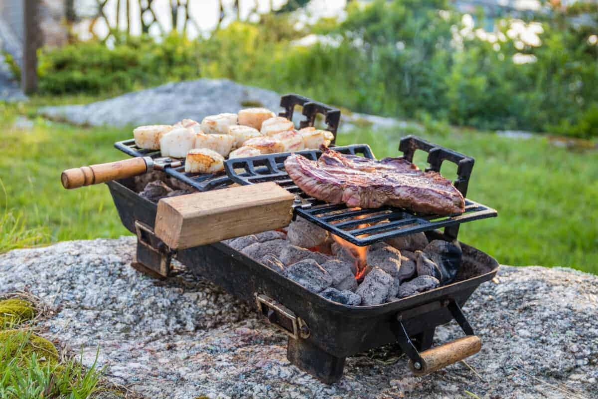 A portable hibachis grill set on a rock in a field