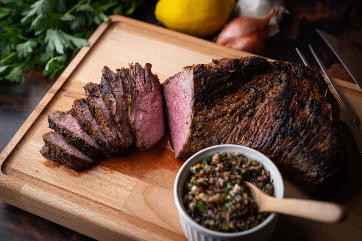 roasted tri tip with bowl of chimichurri sauce