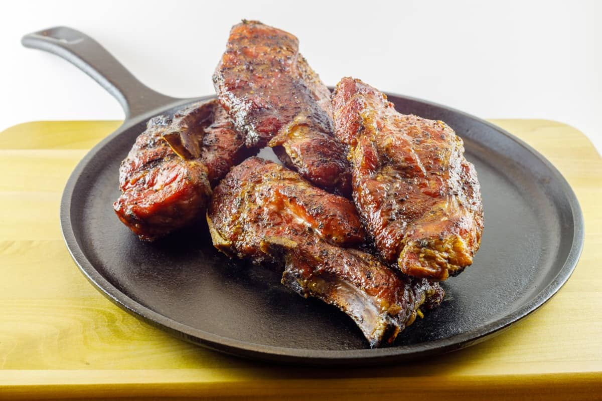 Smoked country style pork ribs served on a seasoned cast iron skillet