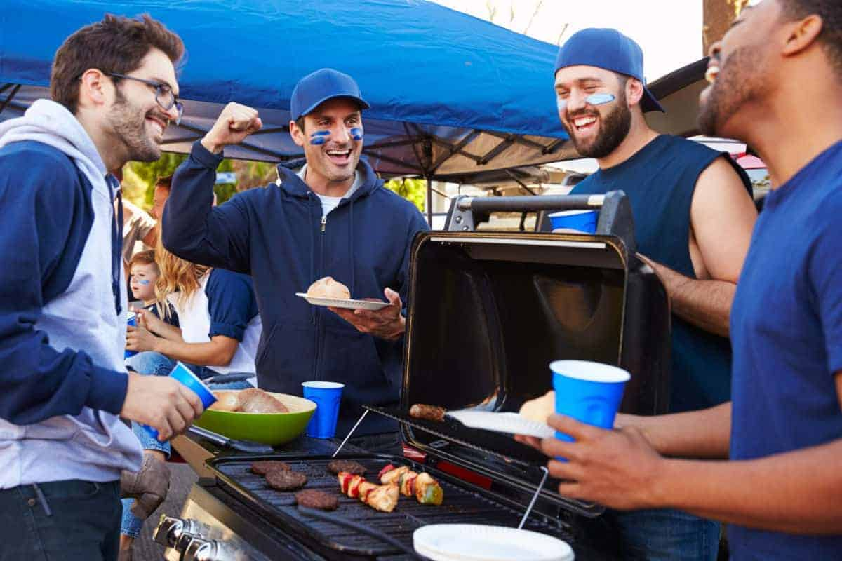 A group of people dressed in blue crowding around a tailgate grill.
