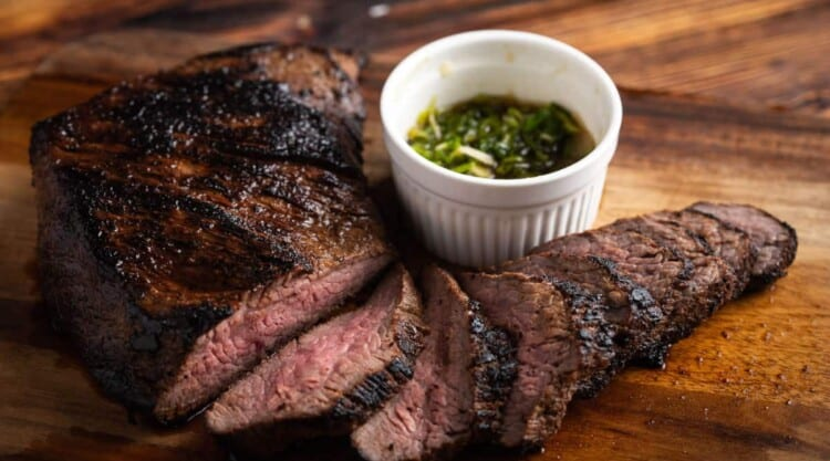 A grilled tri-tip roast, sliced and sitting on a wooden surface