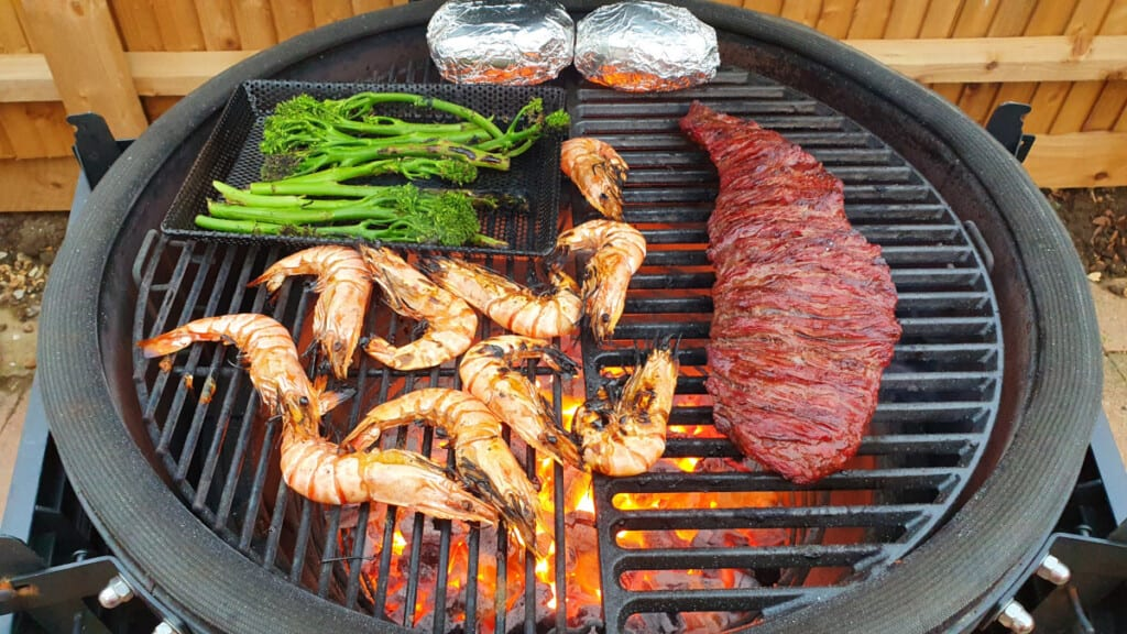 Prawns, foiled potatoes, steak and veg cooking on a kamado grill