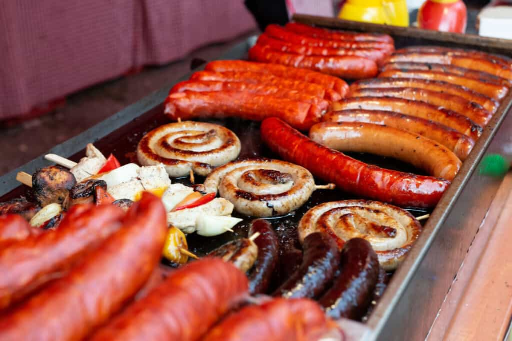 A flat top grill cooking many different types of sausages