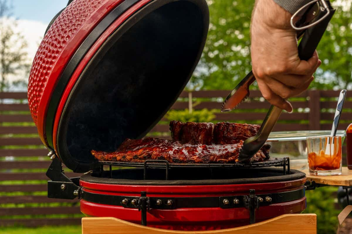 Side view of an open kamado grilling some meats