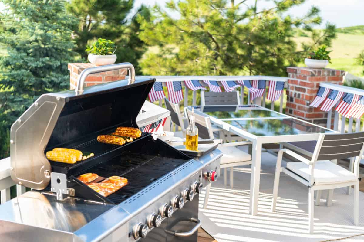 A gas grill on a patio with garden furniture in the background