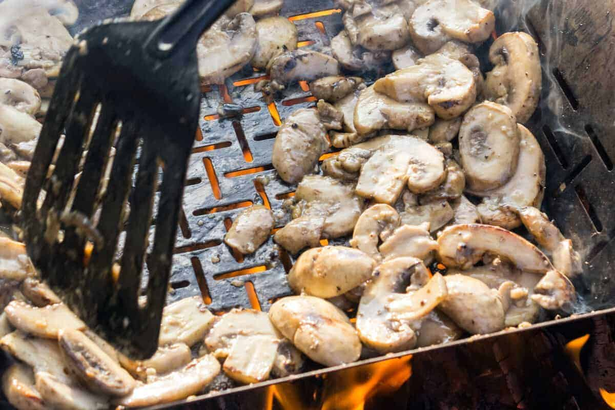 A plastic spatula turning mushrooms on a hot grill