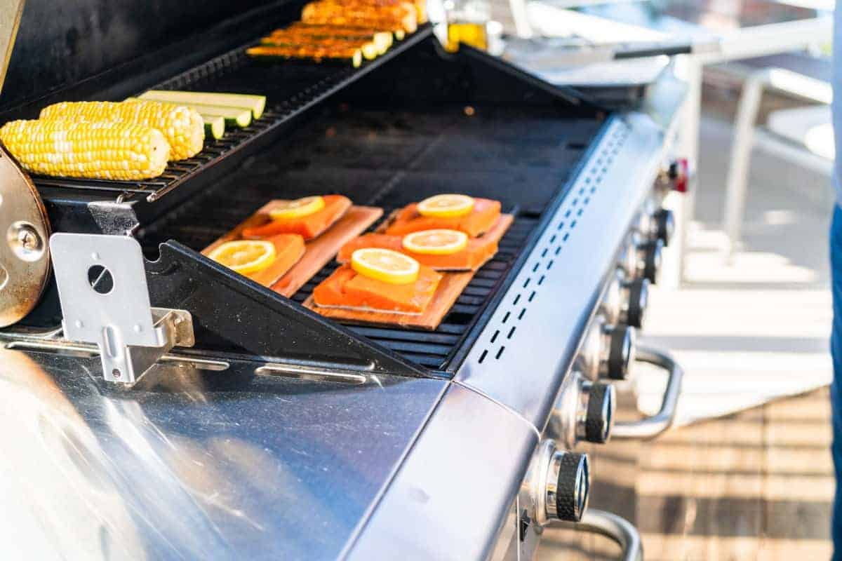 Planked salmon being cooked on a natural gas grill