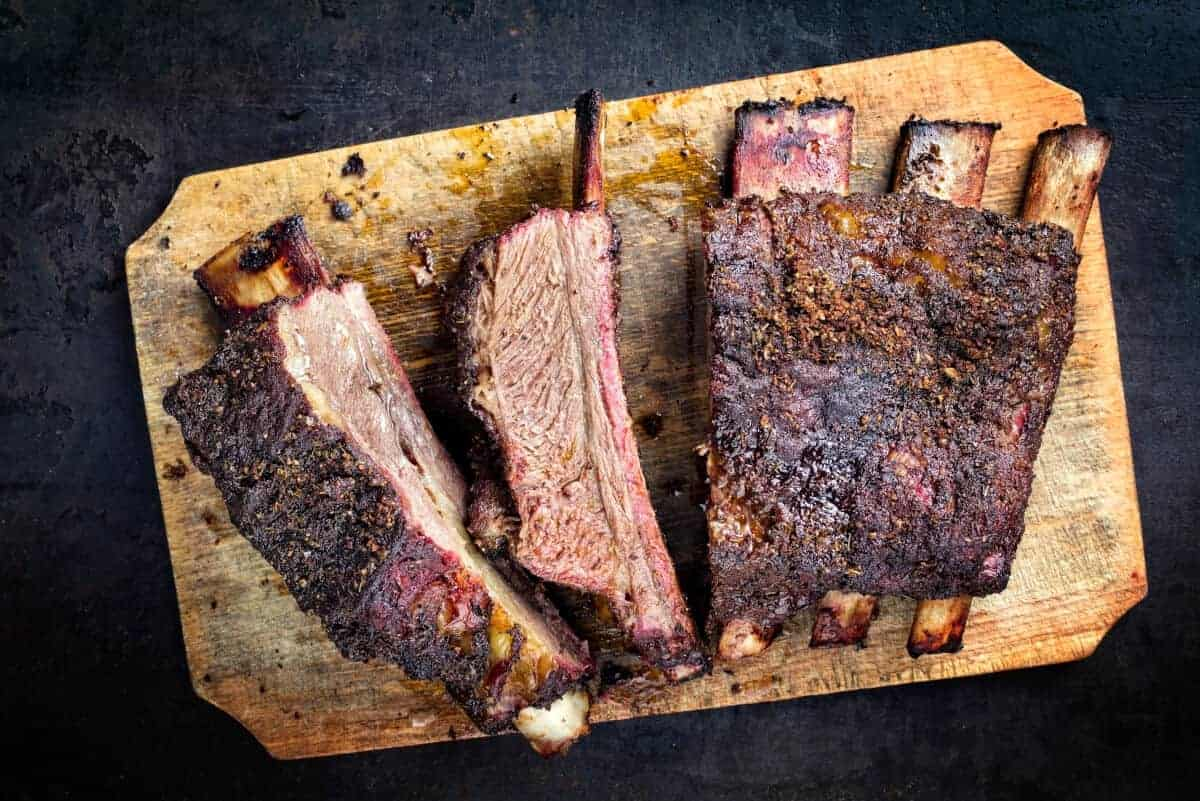 Smoked short ribs, sliced on a wooden cutting board