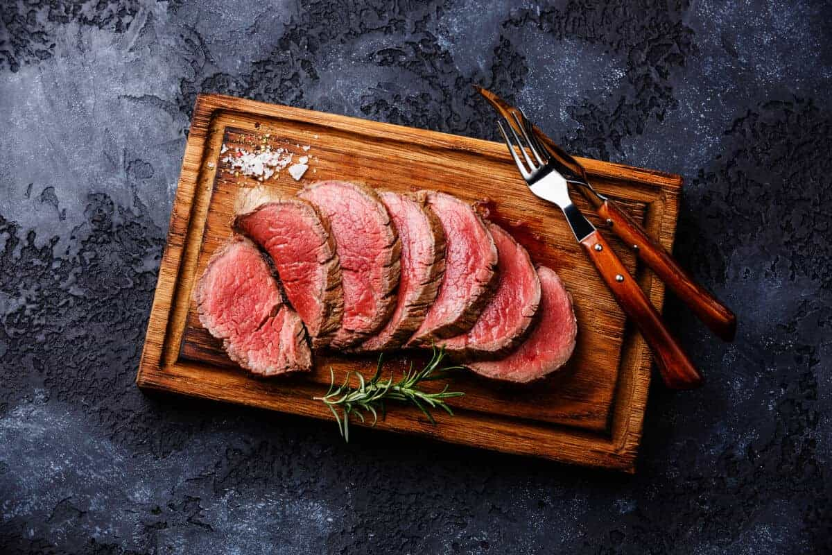 A well smoked, sliced and pink tenderloin roast on a cutting board