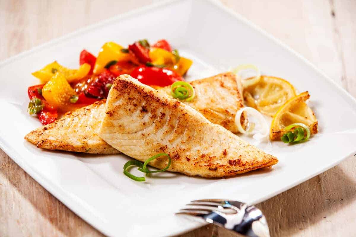 Smoked tilapia filet in a bowl with red and yellow peppers