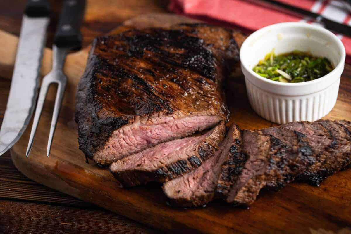 Sliced tri tip, on a cutting board with a knife and ramekin of chimichurri