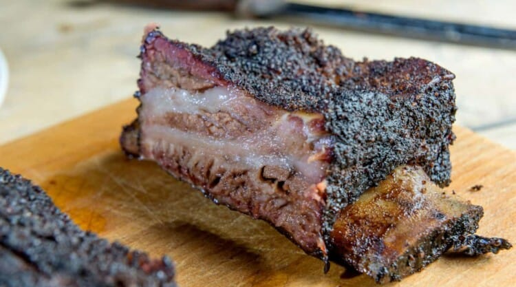 smoked and sliced beef short ribs on a wooden cutting board