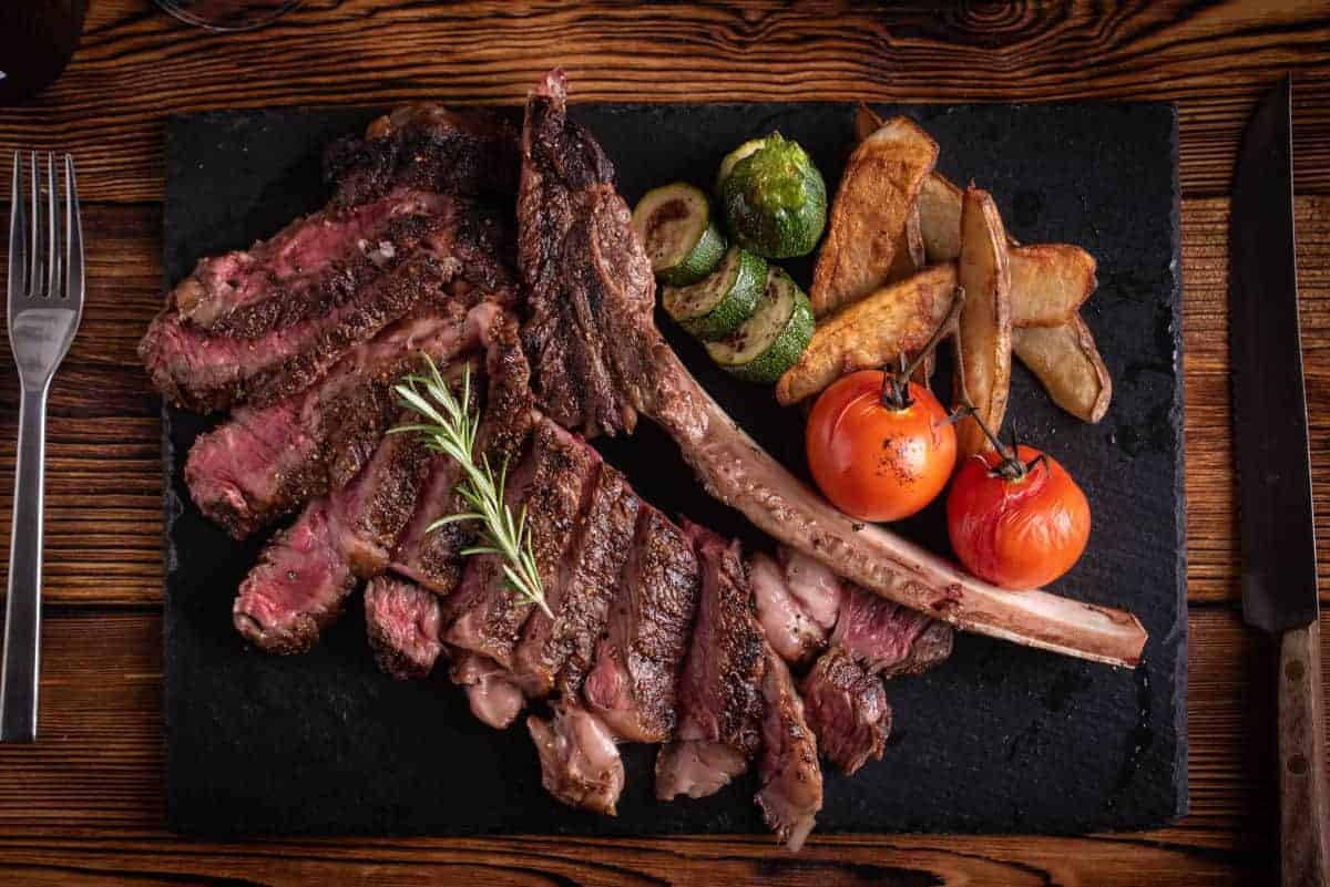 A grilled and sliced tomahawk steak on a cutting board with tomatoes