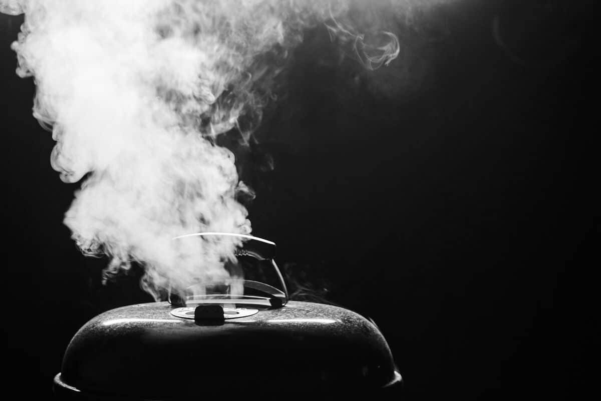 A dark image of a grill with smoke coming out of the top vent
