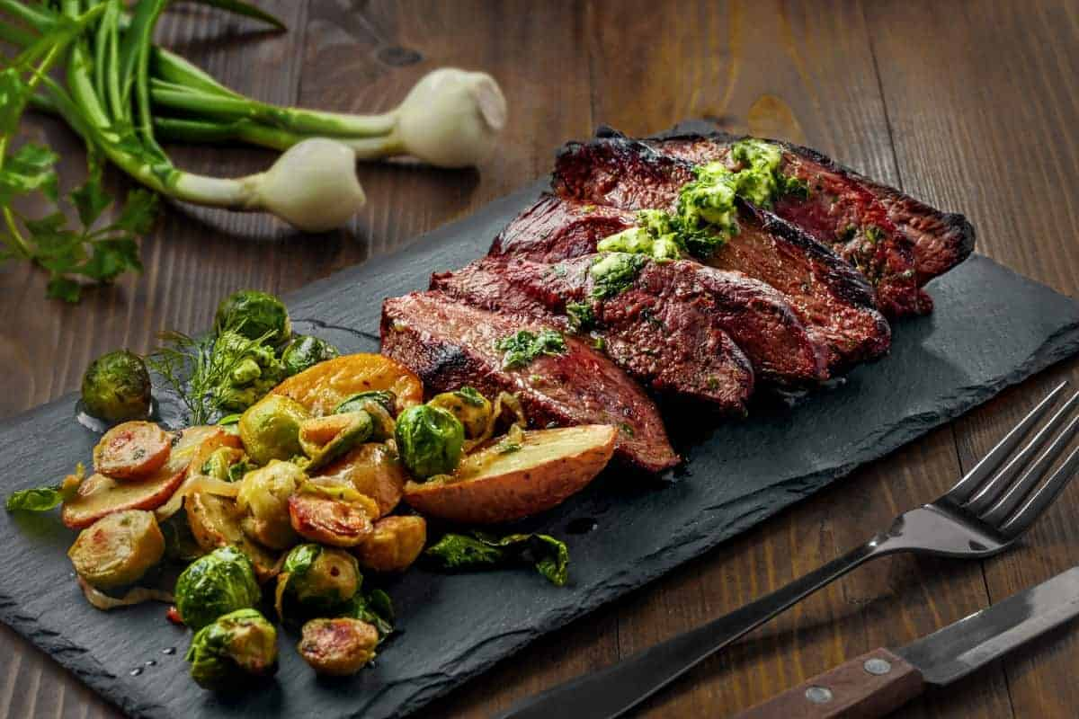 grilled and sliced hanger steak with chimichurri and Brussels sprouts