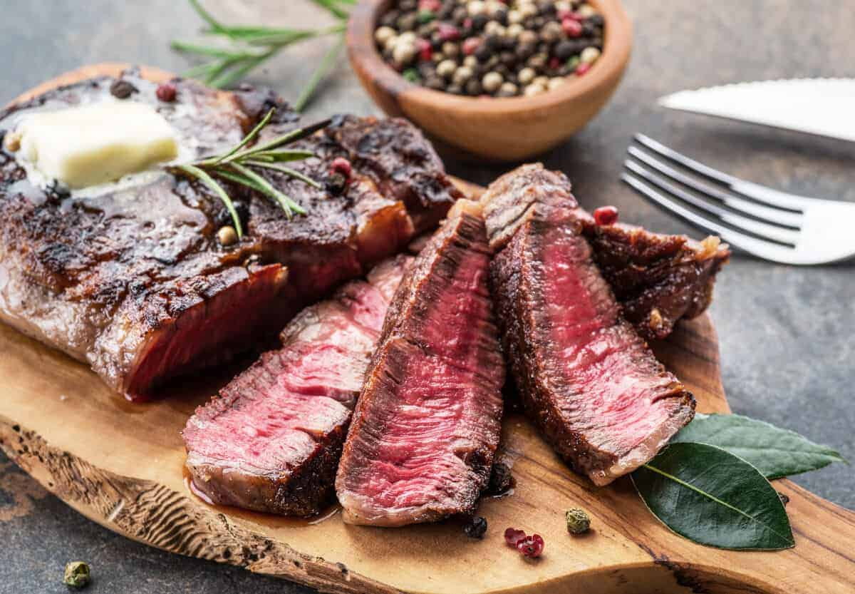 grilled and sliced ribeye steak on a cutting board with peppercorns and herbs