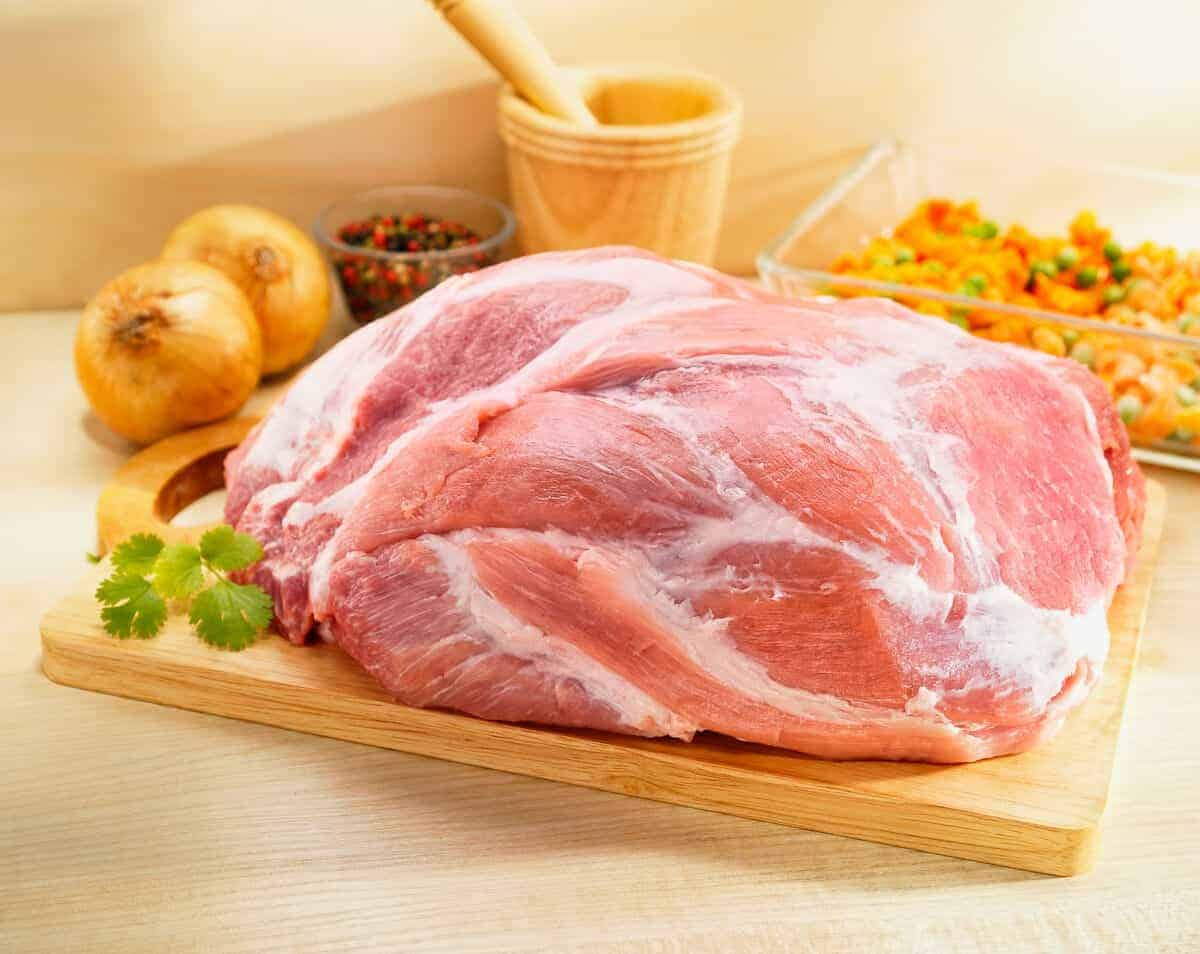 A raw pork picnic ham on a cutting board with onion and herbs