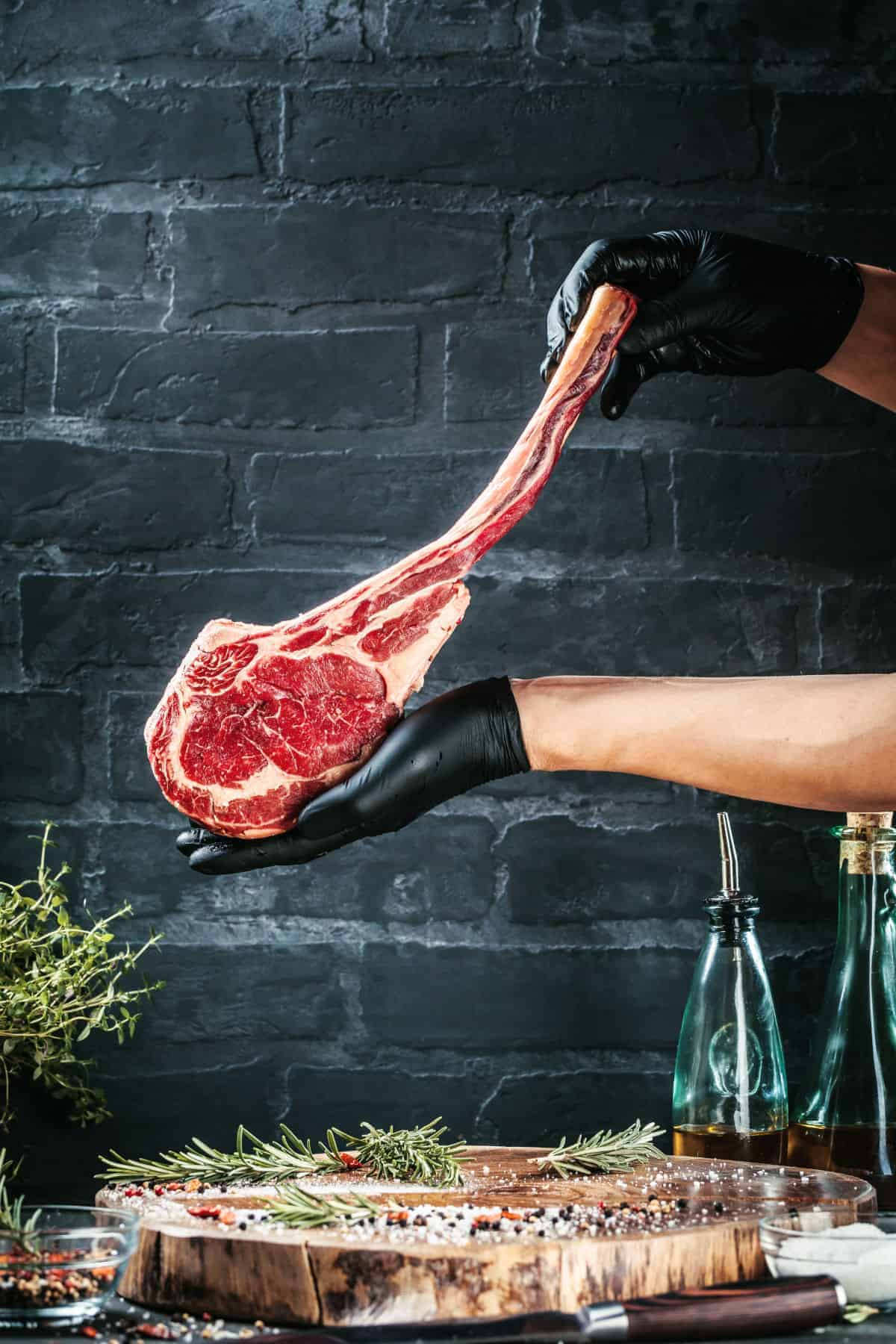 A butchers gloved hands holding up a large tomahawk steak