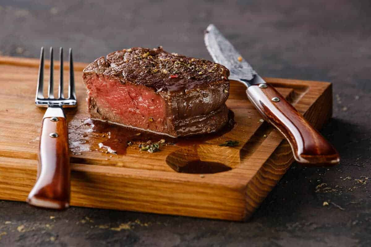A grilled and sliced filet mignon on a cutting board with a knife