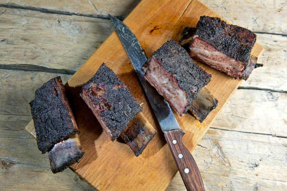 Four smoked beef short ribs, sliced on cutting board with knife
