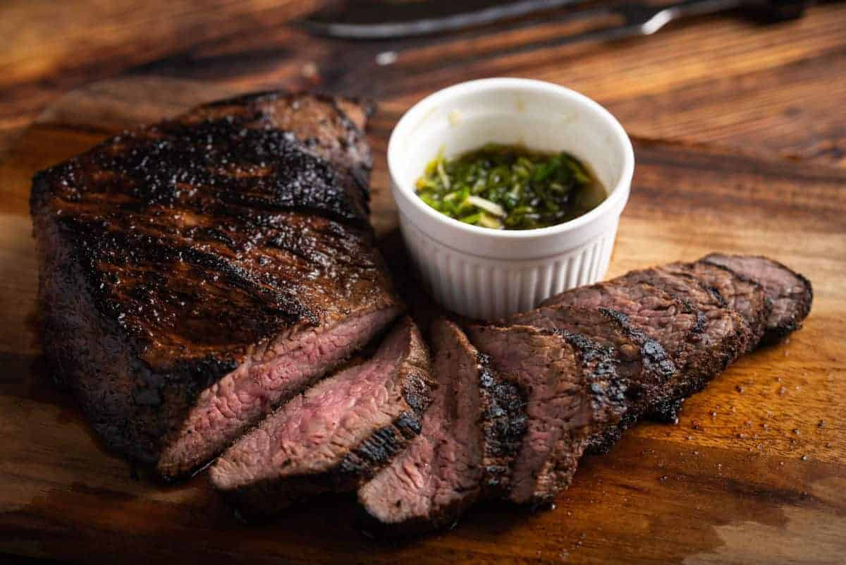 A smoked then sliced tri-tip with a ramekin of chimichurri
