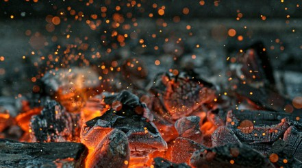 close up of burning lump wood charcoal