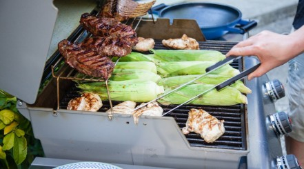 Steak, corn and other items on a large gas grill