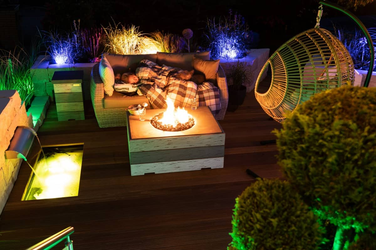 gas fire pit table, lit up in a garden at night