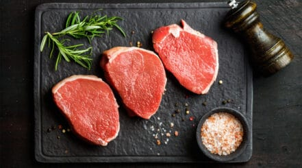 Three raw beef eye of round steaks with rosemary and rock salt on a dark surface