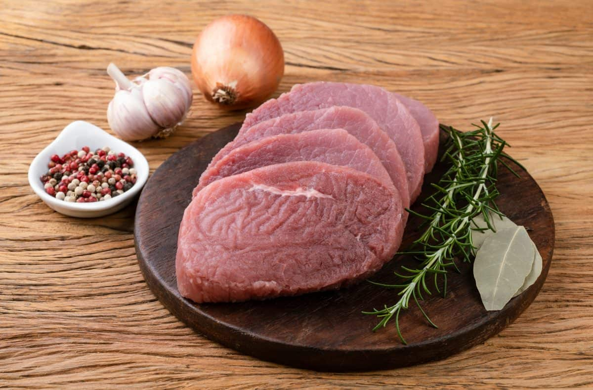 4 eye of round steaks on a wooden cutting board with rosemary