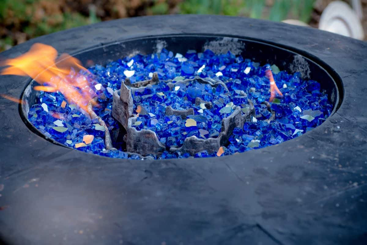 Close up of a lit, propane fueled fire pit filled with blue glass