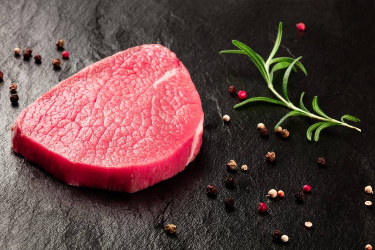 Close up of an round eye steak with rosemary and peppercorns