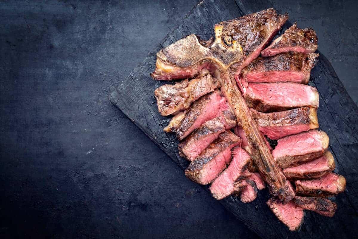 sliced porterhouse steak on a dark background
