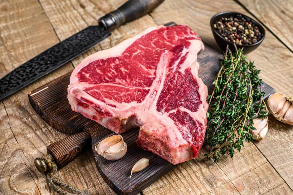 An uncooked porterhouse steak with a bunch ofg thyme on a cutting board