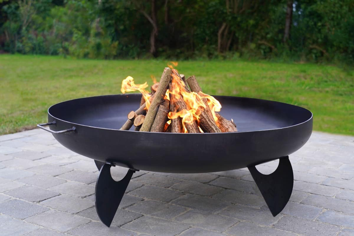 An iron fire pit filled with logs in a pyramid fashion, on fire