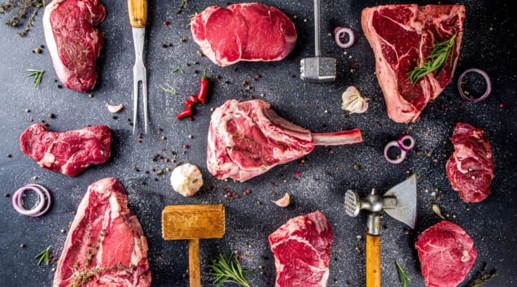 Some of the best steaks for grilling laid out on a dark surface, with spices and kitchen tools