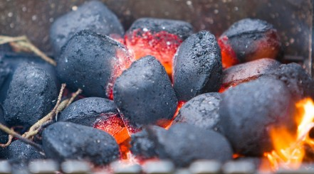 Close up of a small pile of charcoal briquettes being lit from the center