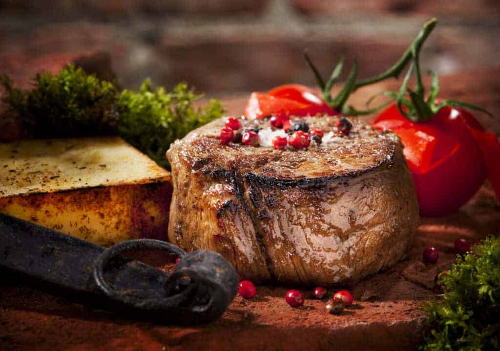 A nicely seared filet mignon steak with tomatoes, herbs and spices