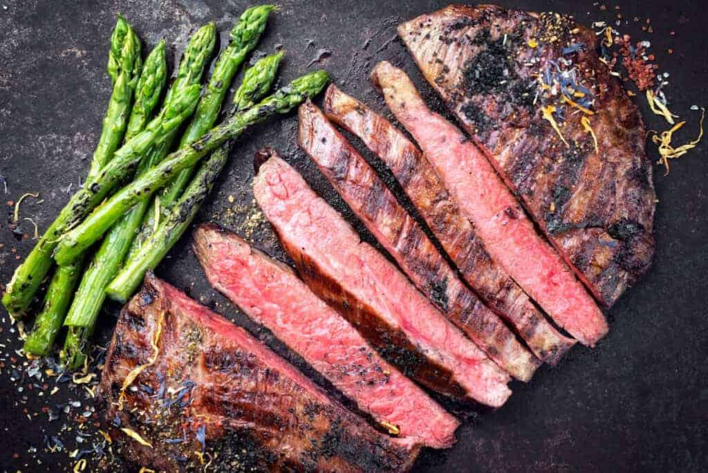 Sliced medium rare flank steak with asparagus