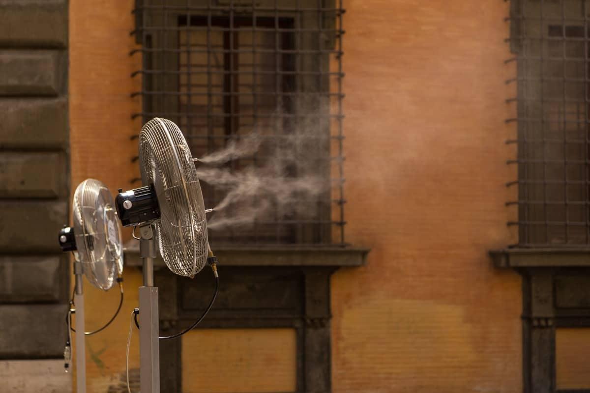 floor standing misting fan blowing water vapor in front of a window