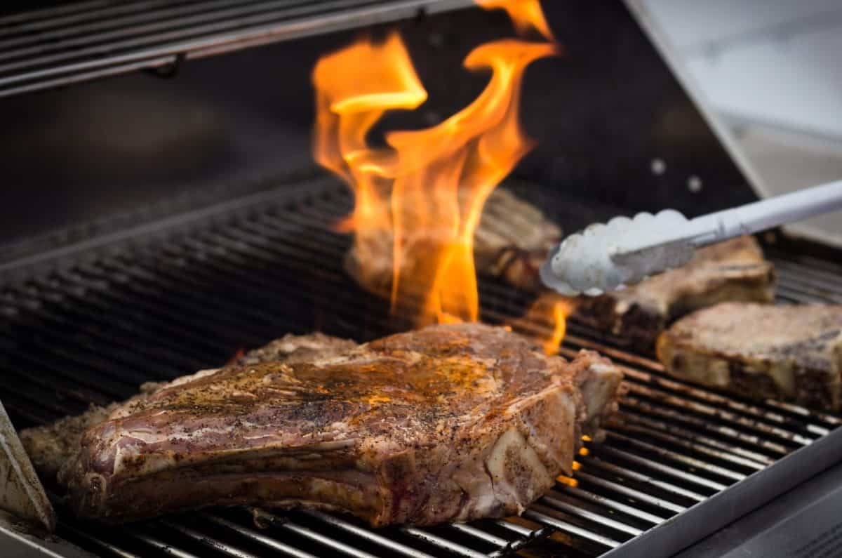 A bone in steak being licked by flames on a grill