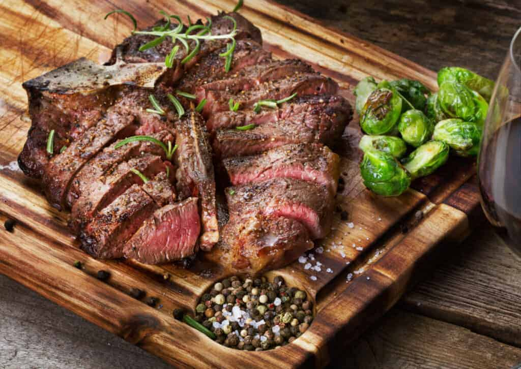 A grilled, sliced porterhouse steak with brussels sprouts