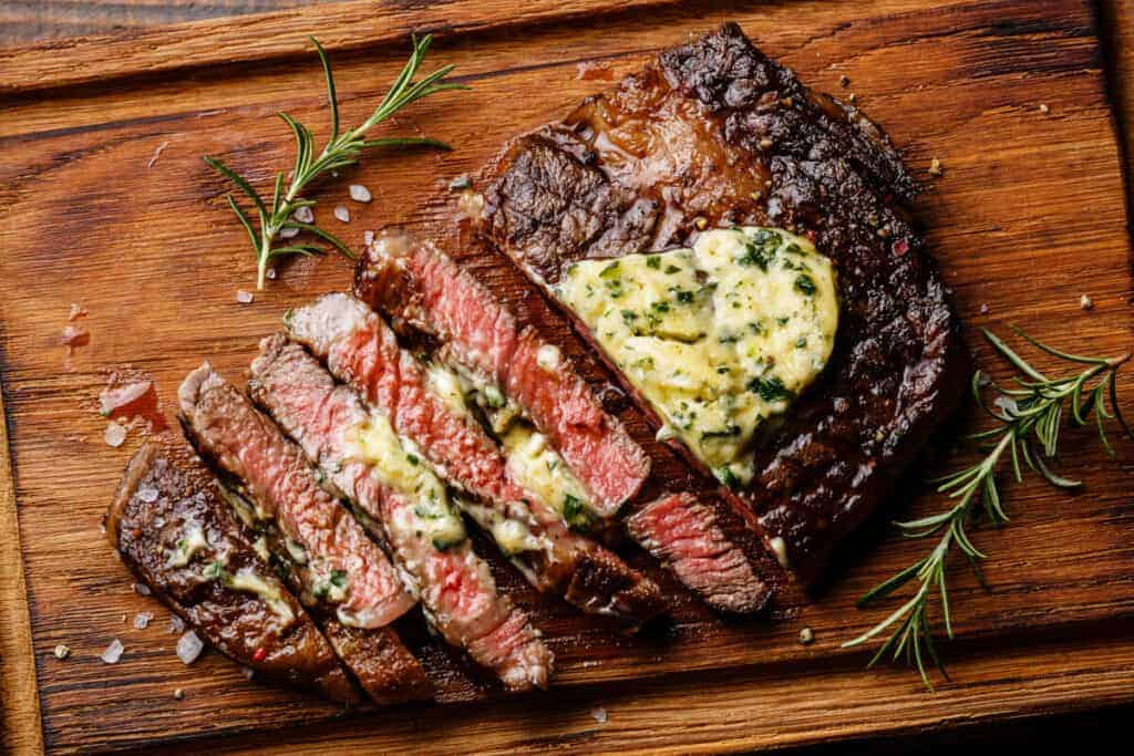 A grilled ribeye steak with melting herb butter on top