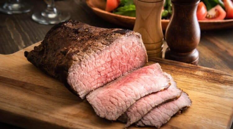 Roasted and sliced bottom round roast on a cutting board