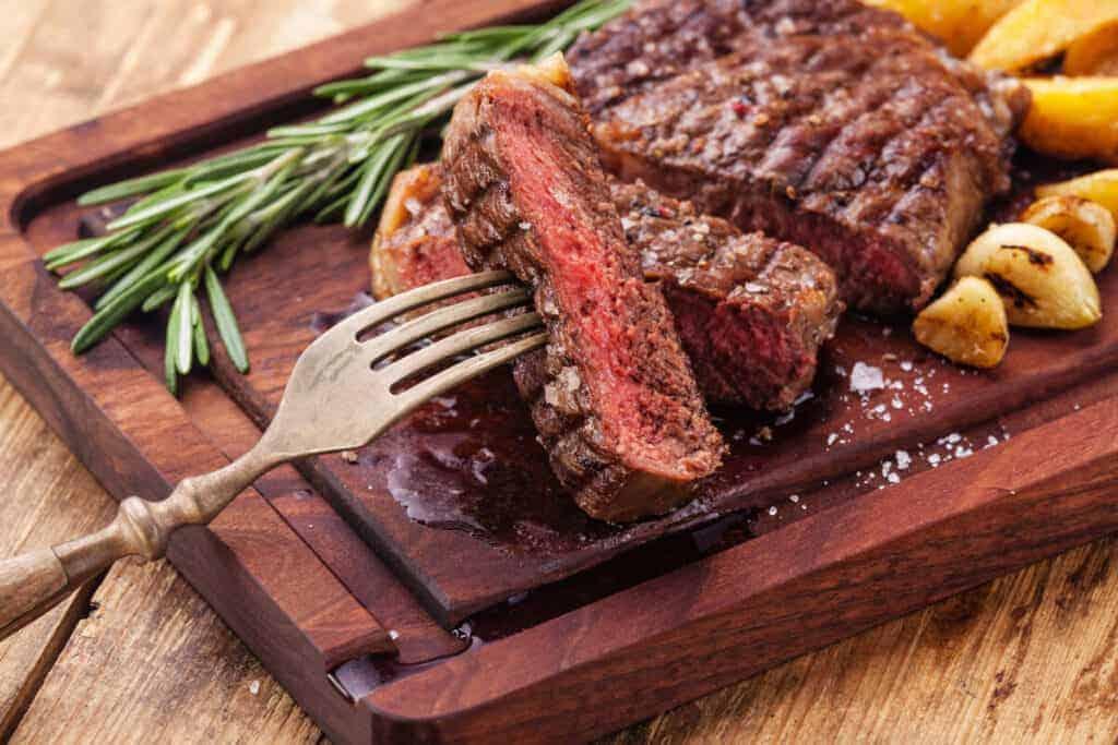 sliced medium rare ribeye steak, with a piece held on a fork