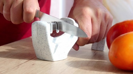 A mans hands pulling a kitchen knife through a 2-stage, white manual knife sharpener