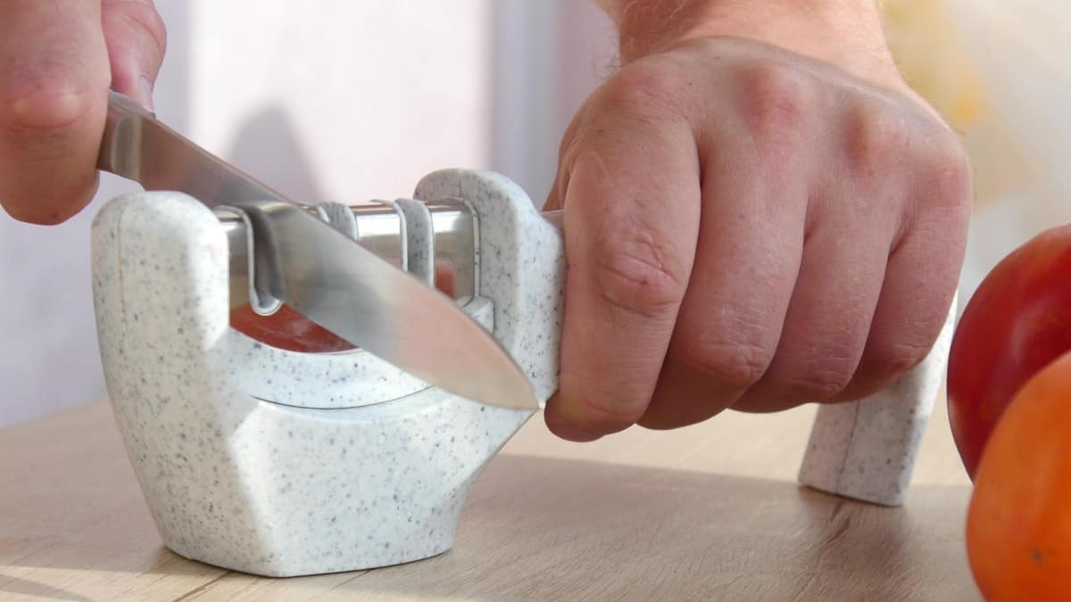 A man pulling a knife through a white manual knife sharpener