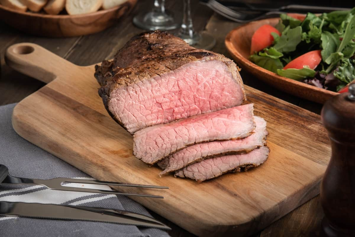 Partially sliced bottom round roast with carving knife and fork set