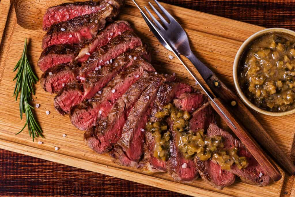 Grilled and sliced ribeye on a cutting board, with knife and fork and a mustard based sauce