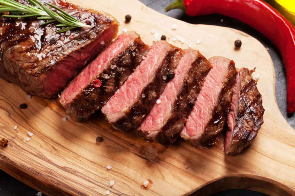 Grilled and sliced medium rare sirloin on a chopping board